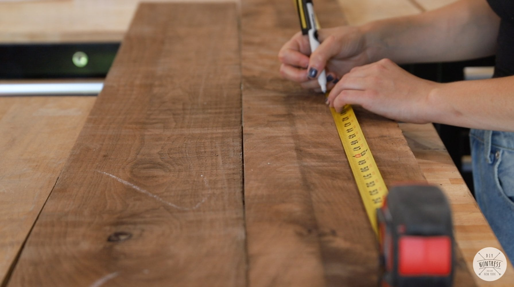 measuring wood with tape measurer
